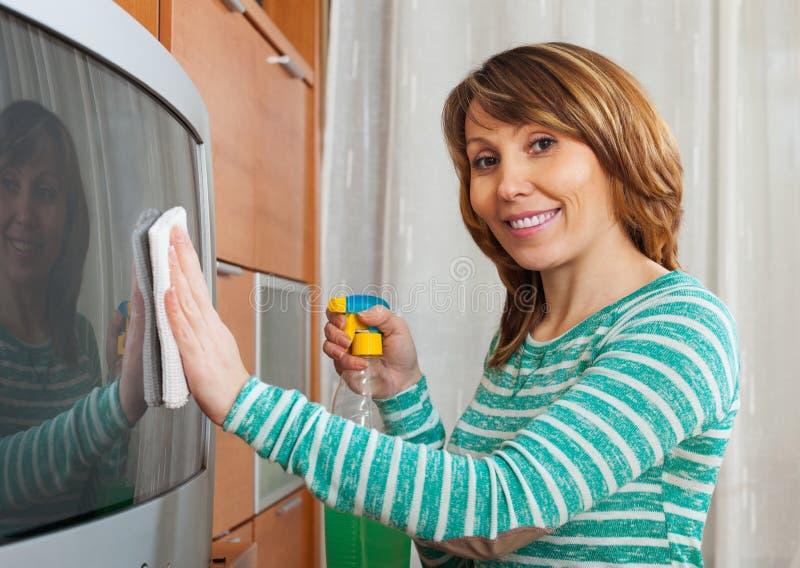 Mujer hermosa que limpia la TV imagenes de archivo