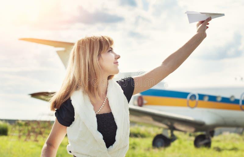 Mujer hermosa que lleva a cabo el avión de papel foto de archivo