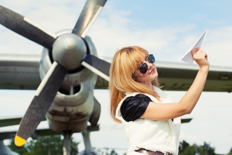 Mujer hermosa que lleva a cabo el avión de papel fotografía de archivo libre de regalías
