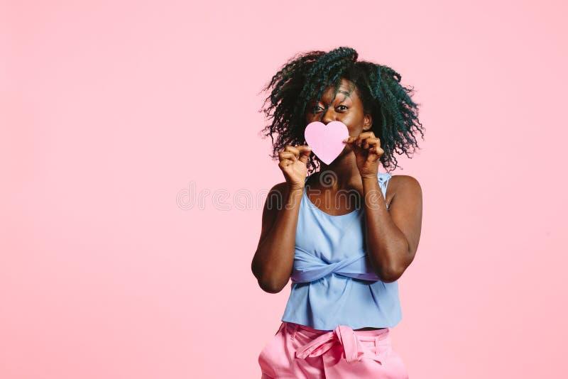 Mujer hermosa que lleva a cabo el corazón rosado delante de ella ojos foto de archivo