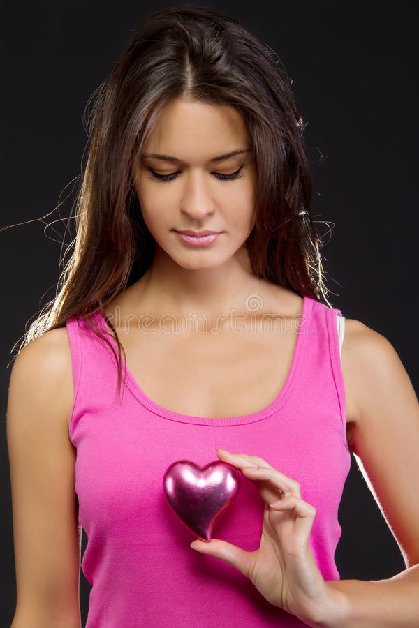 Mujer hermosa que lleva a cabo un corazón fotografía de archivo