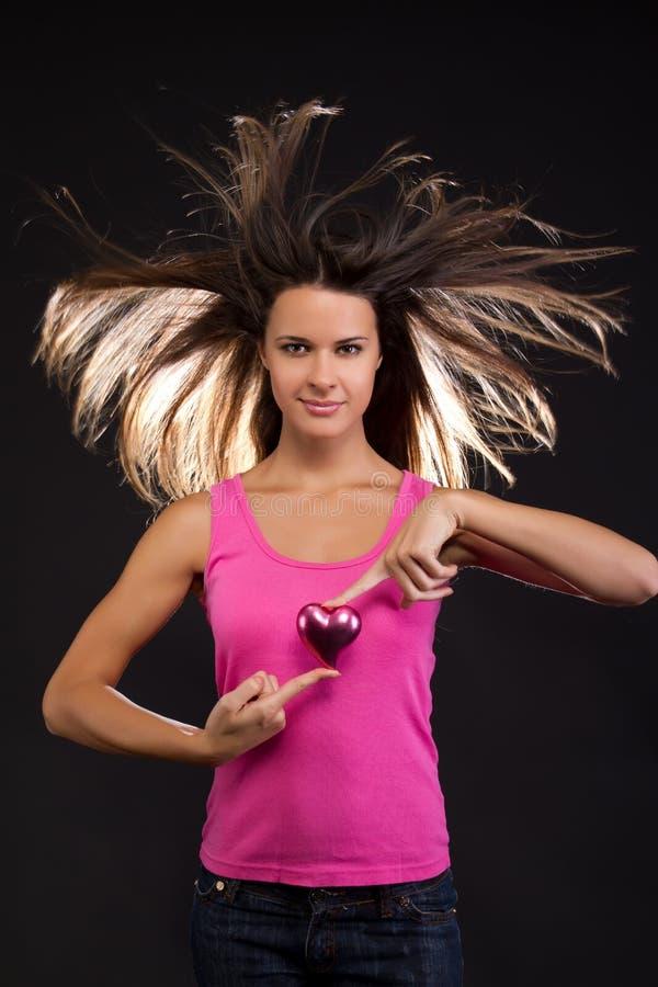 Mujer hermosa que lleva a cabo un corazón fotografía de archivo libre de regalías
