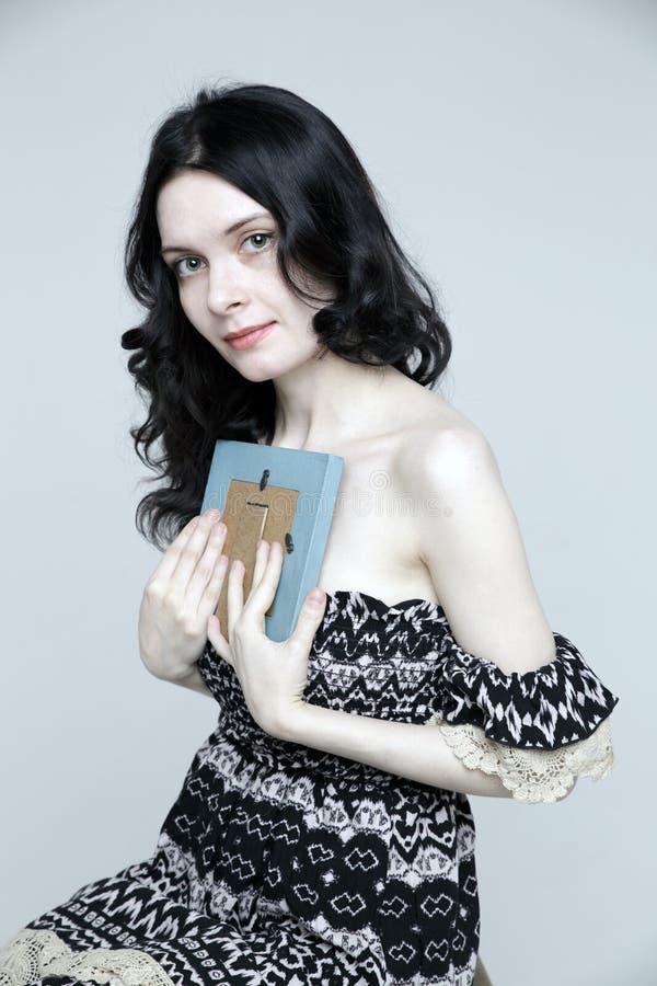Mujer hermosa que lleva a cabo un marco fotografía de archivo libre de regalías