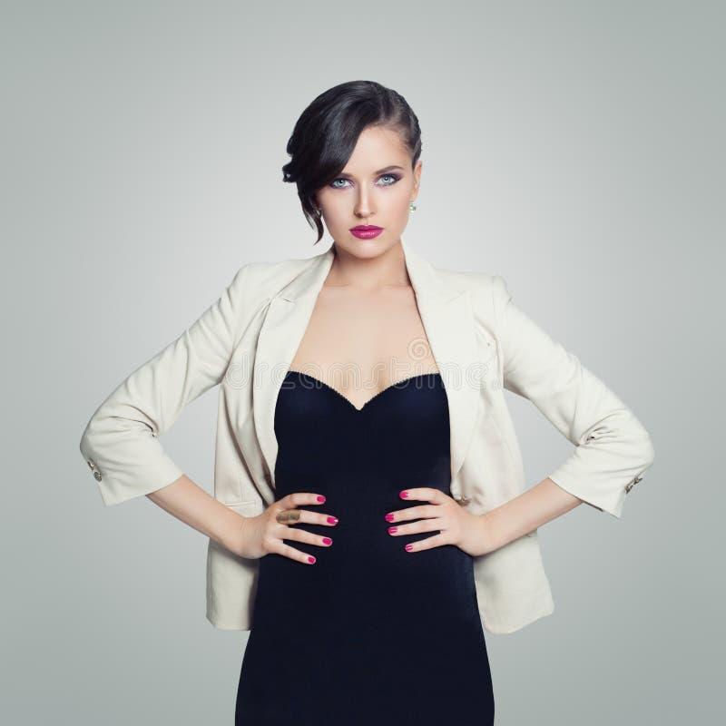 Mujer hermosa que lleva el vestido negro que presenta en el fondo blanco fotos de archivo