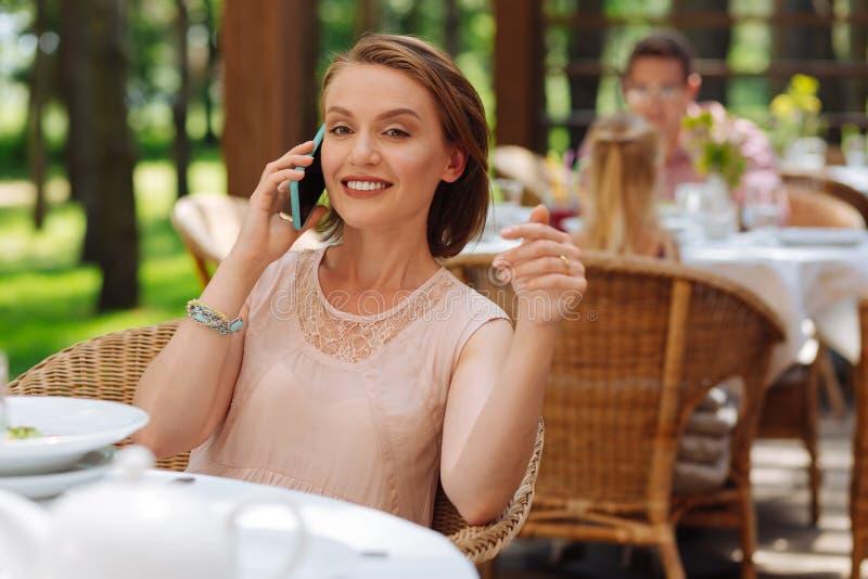 Mujer hermosa que lleva la pulsera agradable que llama a su amigo imágenes de archivo libres de regalías