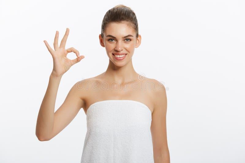 Mujer hermosa que lleva una toalla con la cara feliz que sonríe haciendo la muestra aceptable con la mano aislada con el fondo bl fotos de archivo