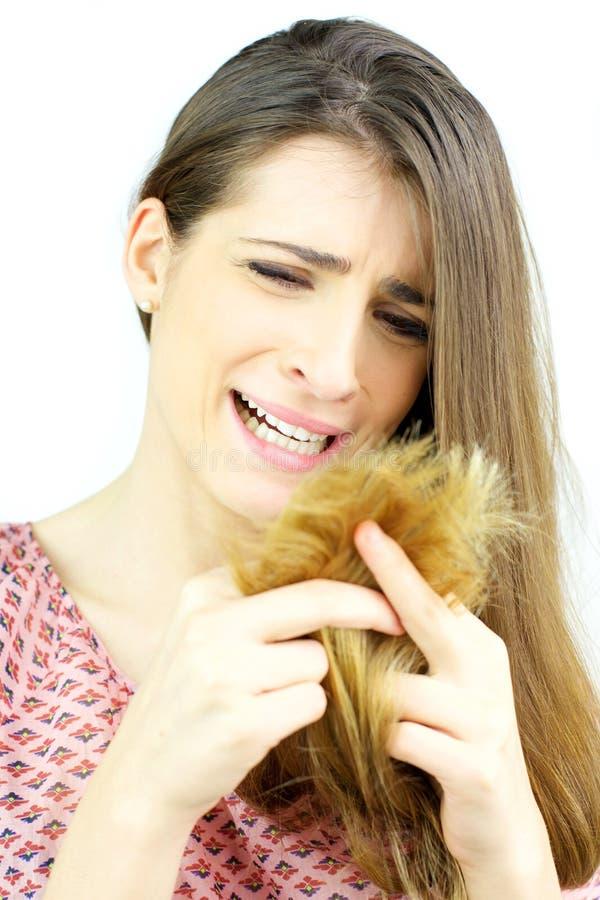 Mujer hermosa que llora mirando el pelo de los extremos partidos aislado imagen de archivo libre de regalías
