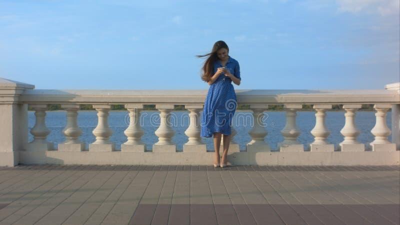Mujer hermosa que manda un SMS en el teléfono en la costa foto de archivo libre de regalías