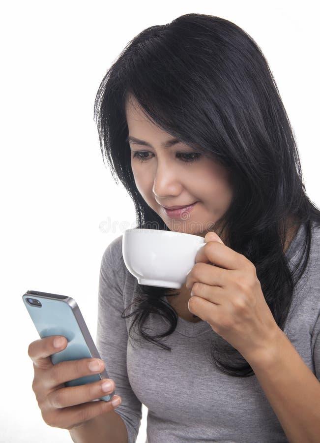 Mujer hermosa que manda un SMS en el teléfono móvil y el drinki fotografía de archivo libre de regalías