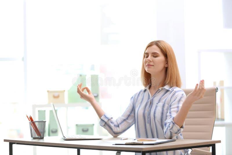 Mujer hermosa que medita en la tabla en oficina durante rotura Yoga del zen imagen de archivo
