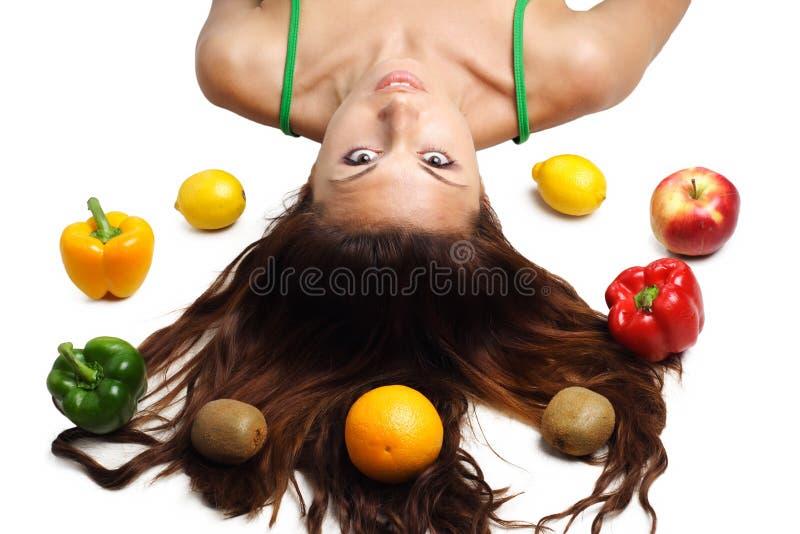 Mujer hermosa que miente con las frutas y el pelo imágenes de archivo libres de regalías