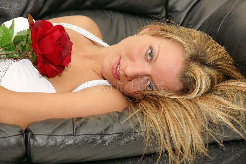 Mujer hermosa que miente en el sofá y que sostiene la rosa del rojo imagen de archivo