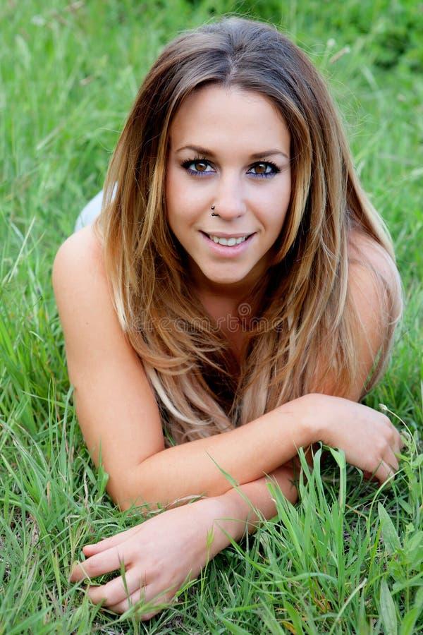 Mujer hermosa que miente en la hierba imagen de archivo libre de regalías