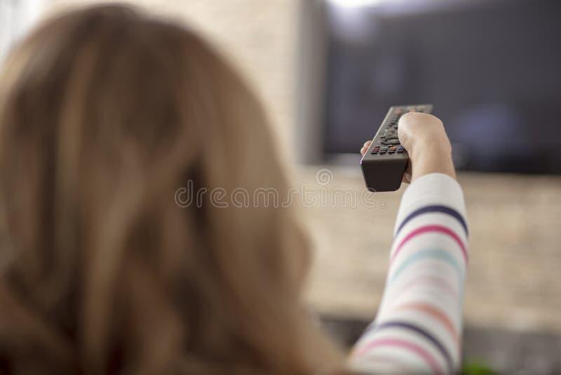 Mujer hermosa que miente en un sofá con la televisión teledirigida y de observación imágenes de archivo libres de regalías