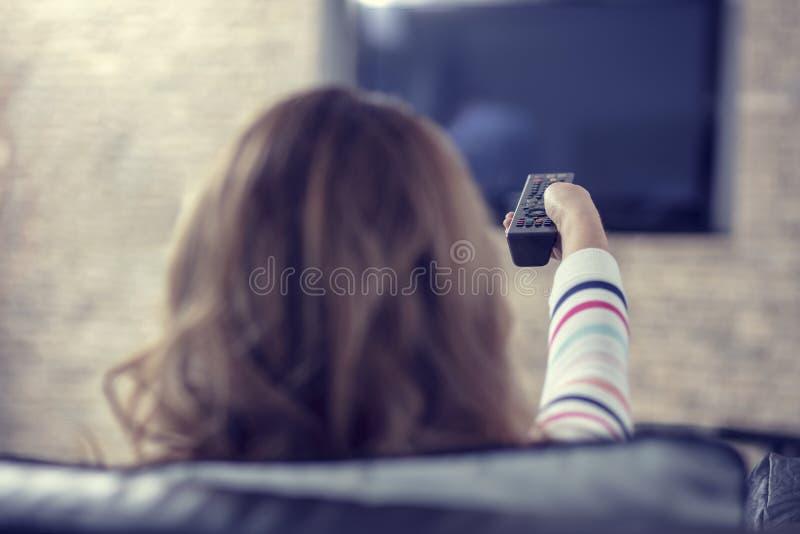 Mujer hermosa que miente en un sofá con la televisión teledirigida y de observación imagenes de archivo