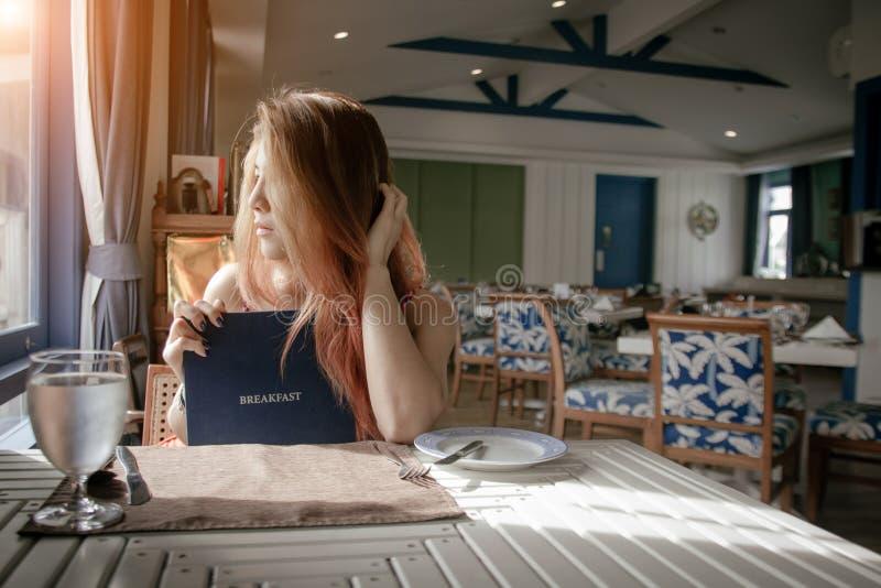 Mujer hermosa que mira el menú del restaurante que decide qué ordenar imagen de archivo libre de regalías