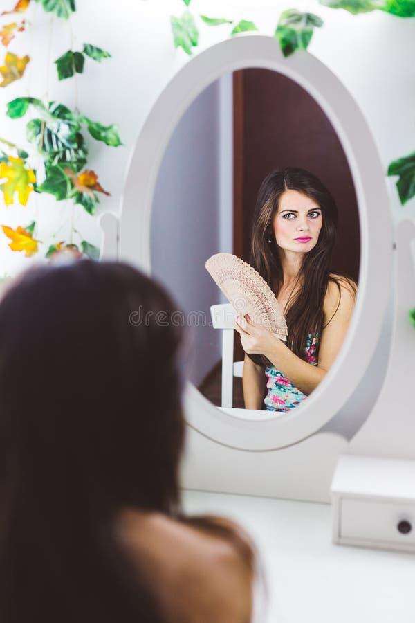 Mujer hermosa que mira en el espejo foto de archivo