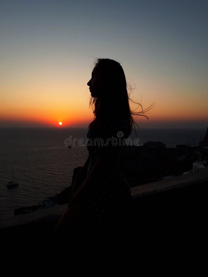 Mujer hermosa que mira puesta del sol anaranjada colorida en Oia, Santorini, Grecia foto de archivo