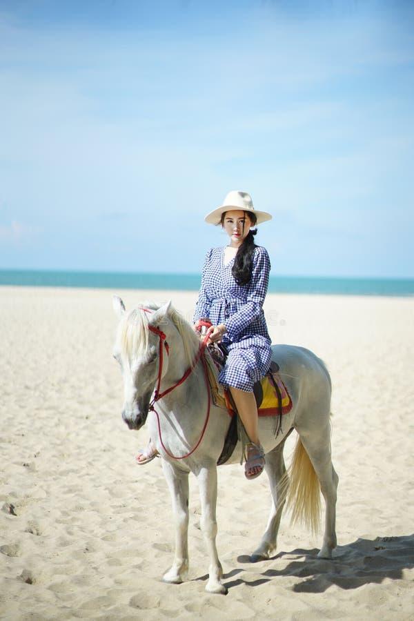 Mujer hermosa que monta un caballo en la playa imagenes de archivo