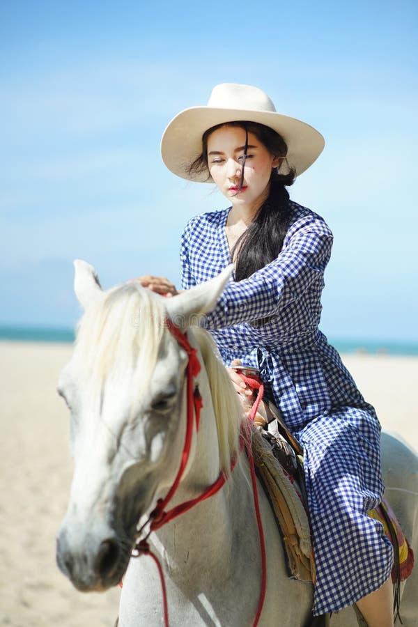 Mujer hermosa que monta un caballo en la playa foto de archivo
