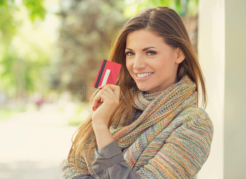 Mujer hermosa que muestra la nueva tarjeta de crédito fotografía de archivo