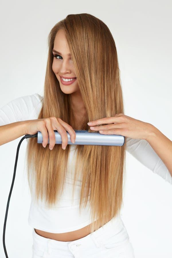 Mujer hermosa que plancha el pelo recto largo con la enderezadora imagenes de archivo
