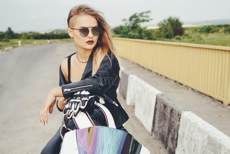 Mujer hermosa que presenta con las gafas de sol en una moto imagenes de archivo