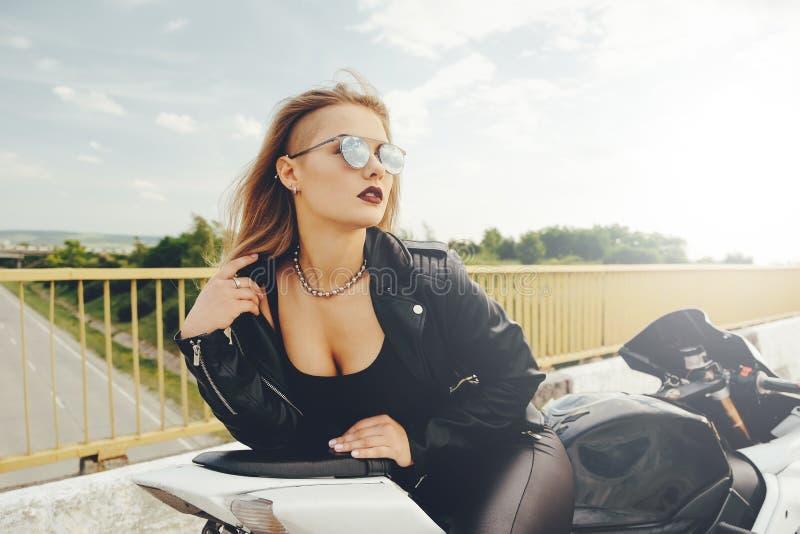 Mujer hermosa que presenta con las gafas de sol en una moto fotos de archivo libres de regalías