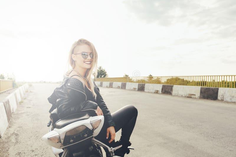 Mujer hermosa que presenta con las gafas de sol en una moto foto de archivo