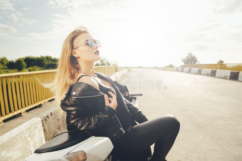 Mujer hermosa que presenta con las gafas de sol en una moto foto de archivo libre de regalías