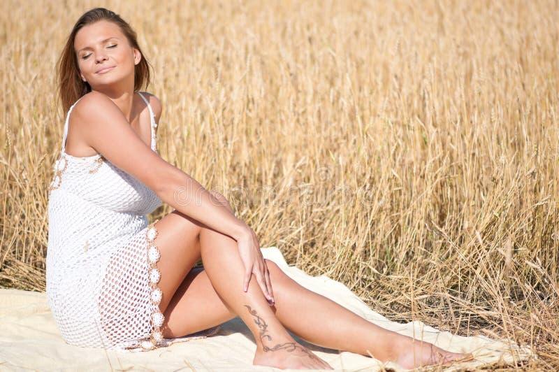 Mujer hermosa que presenta en campo de trigo. Comida campestre. fotos de archivo