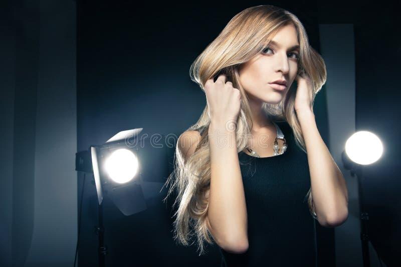 Mujer hermosa que presenta en el estudio en flashes ligeros fotografía de archivo