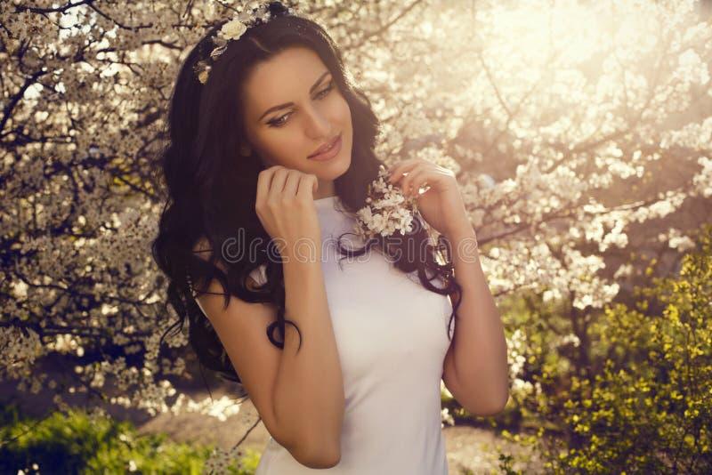 Mujer hermosa que presenta en el parque del flor de la primavera imagen de archivo libre de regalías