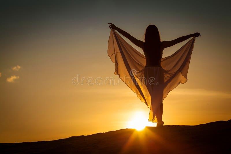 Mujer hermosa que presenta en la puesta del sol imagen de archivo