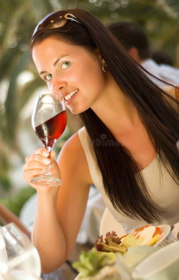 Mujer hermosa que prueba el vino rojo en el restaurante imagen de archivo