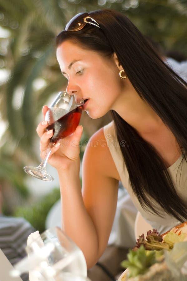 Mujer hermosa que prueba el vino rojo en el restaurante foto de archivo libre de regalías