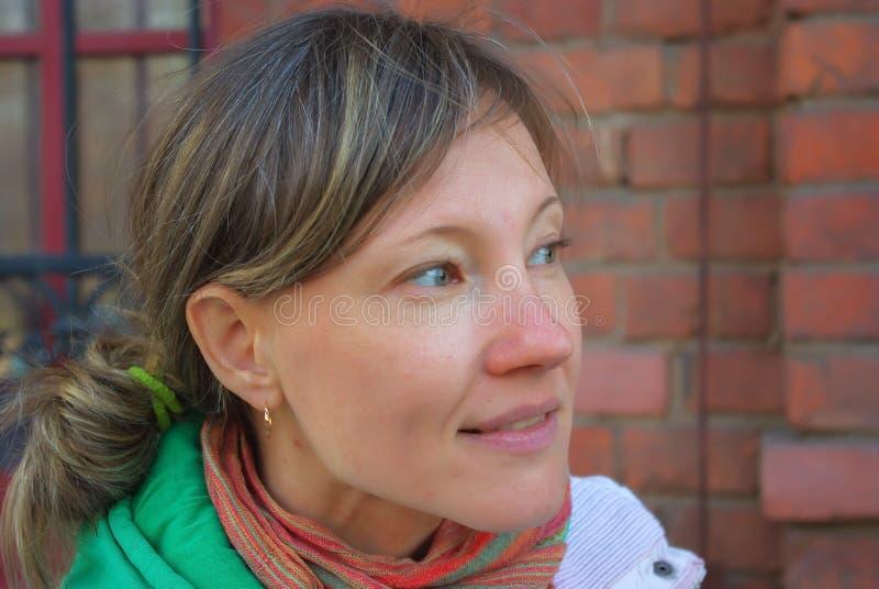 Mujer hermosa que ríe al aire libre feliz con un fondo de la pared de ladrillo fotografía de archivo libre de regalías