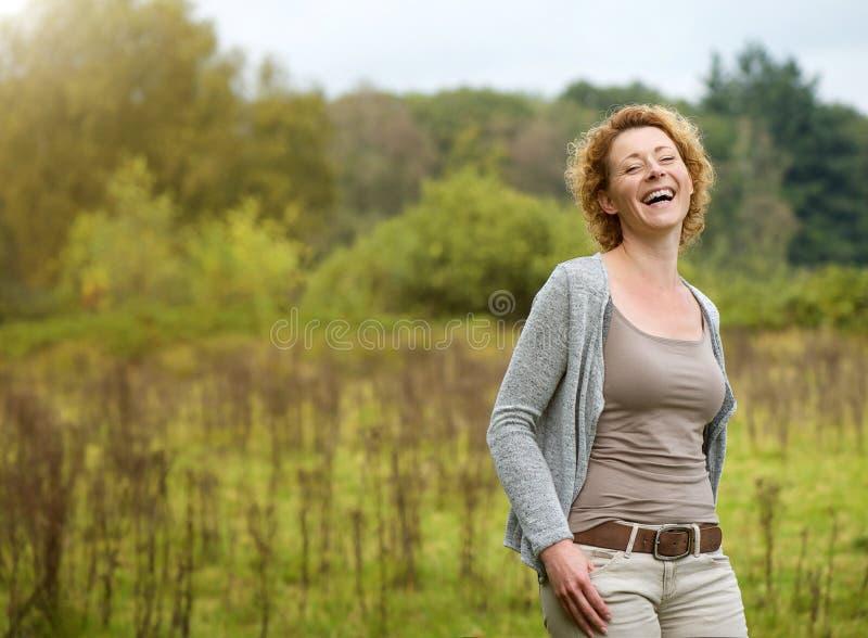 Mujer hermosa que ríe en el campo fotos de archivo