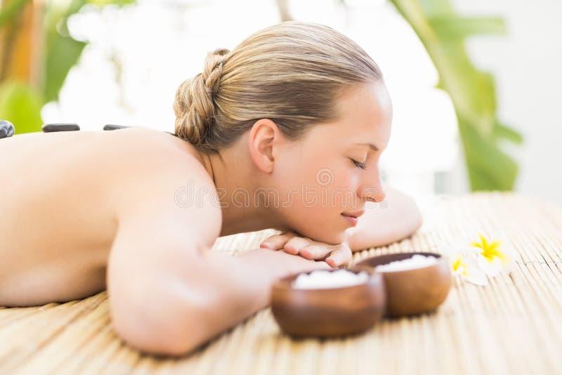 Mujer hermosa que recibe el masaje de piedra en el centro del balneario imagen de archivo