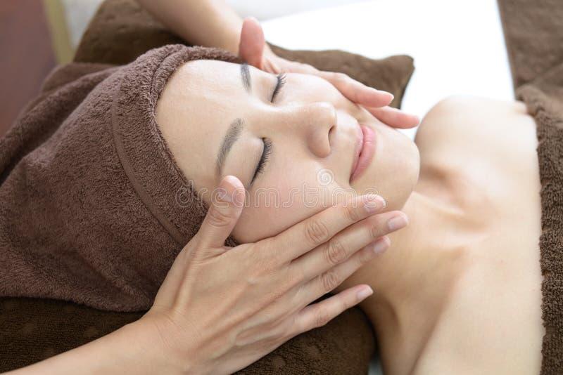Mujer hermosa que recibe masaje facial fotos de archivo libres de regalías