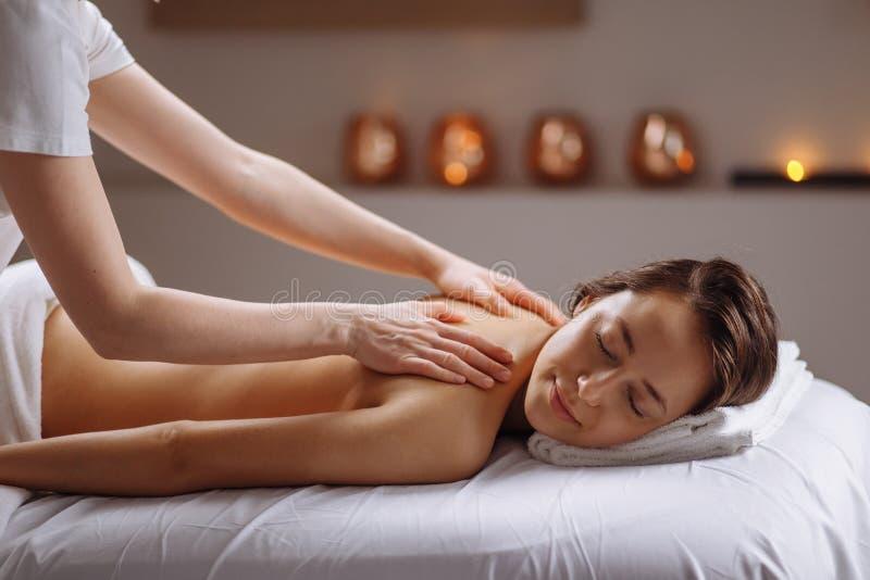 Mujer hermosa que recibe un masaje trasero de relajación en el balneario fotografía de archivo