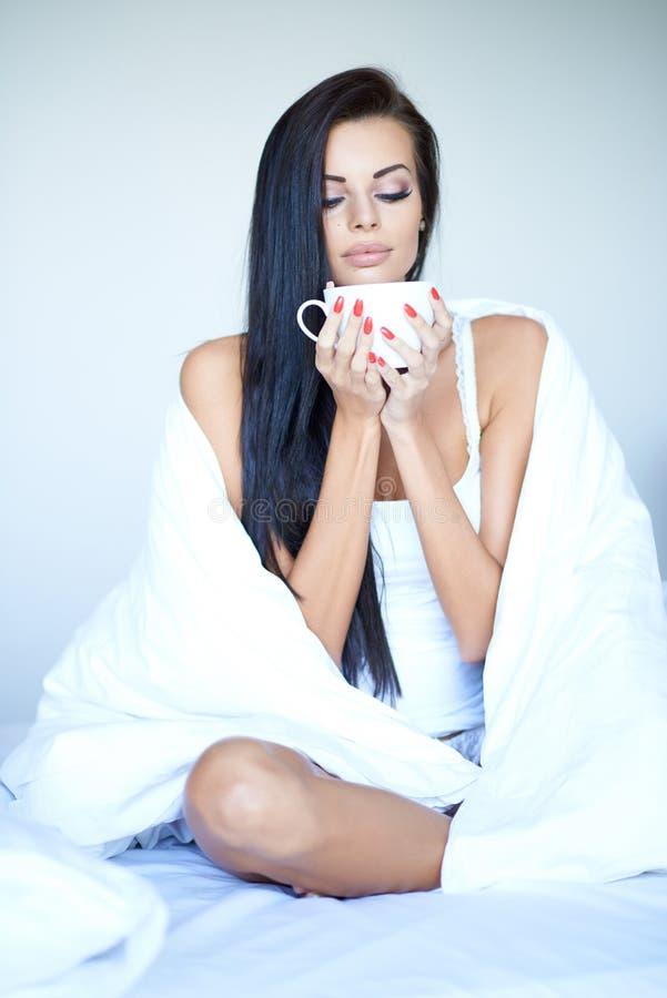 Mujer hermosa que saborea una taza de café en cama foto de archivo