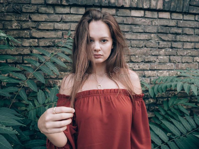 Mujer hermosa que se coloca al aire libre en la pared de ladrillo del rustick fotografía de archivo
