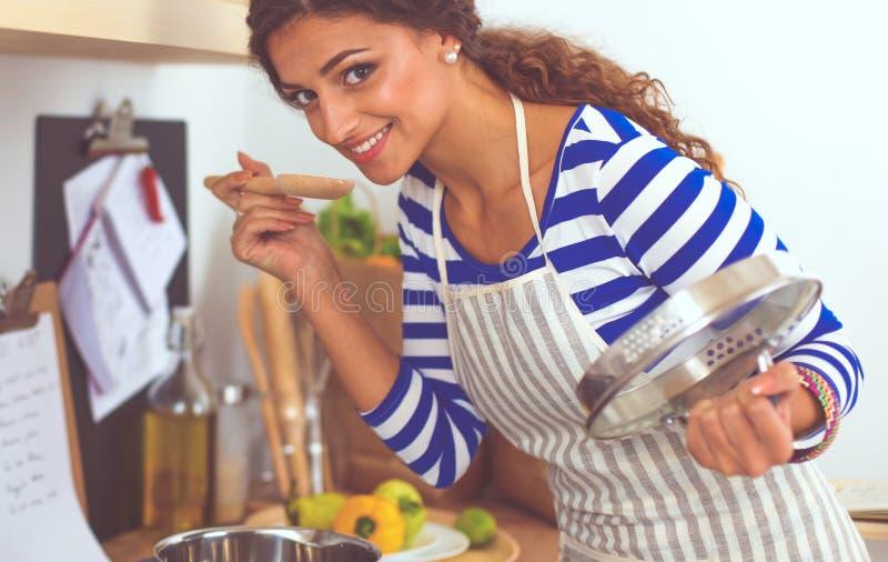 Mujer hermosa que se coloca en cocina con el delantal imagenes de archivo