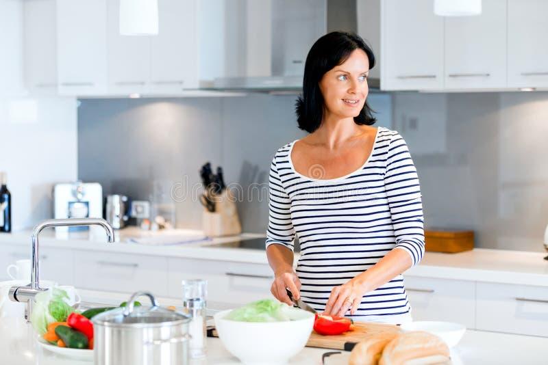 Mujer hermosa que se coloca en la cocina y la sonrisa foto de archivo