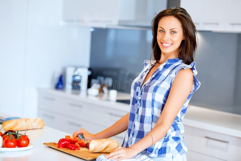Mujer hermosa que se coloca en la cocina y la sonrisa fotografía de archivo libre de regalías