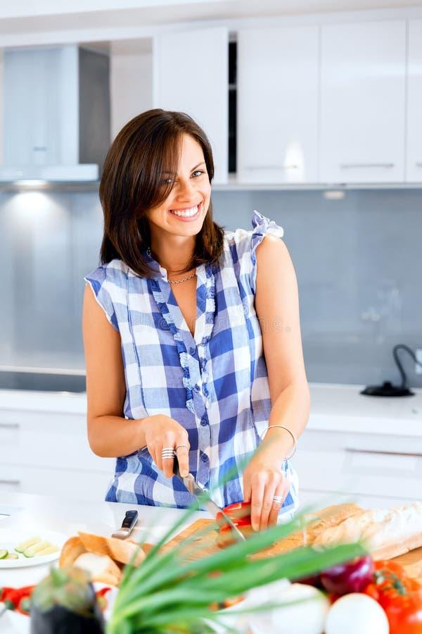 Mujer hermosa que se coloca en la cocina y la sonrisa fotografía de archivo