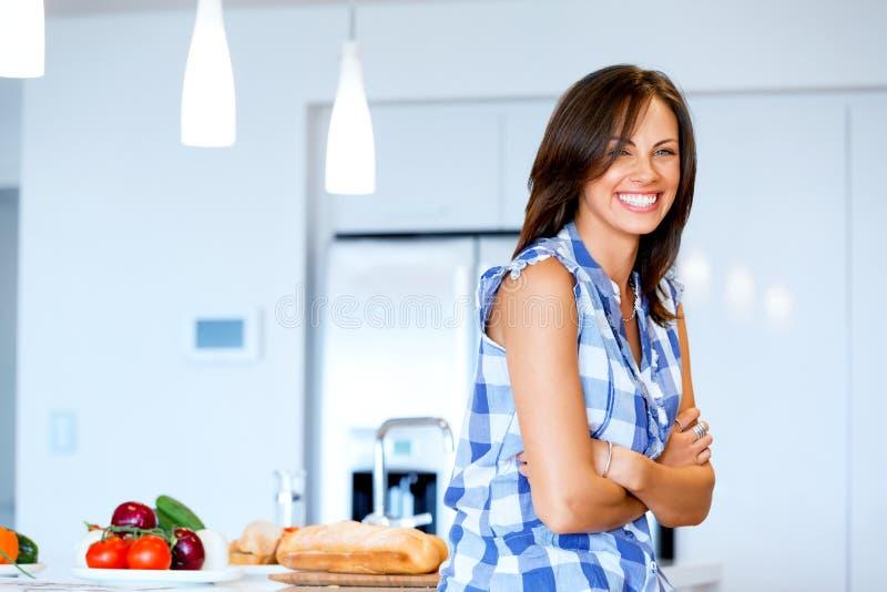 Mujer hermosa que se coloca en la cocina y la sonrisa imágenes de archivo libres de regalías
