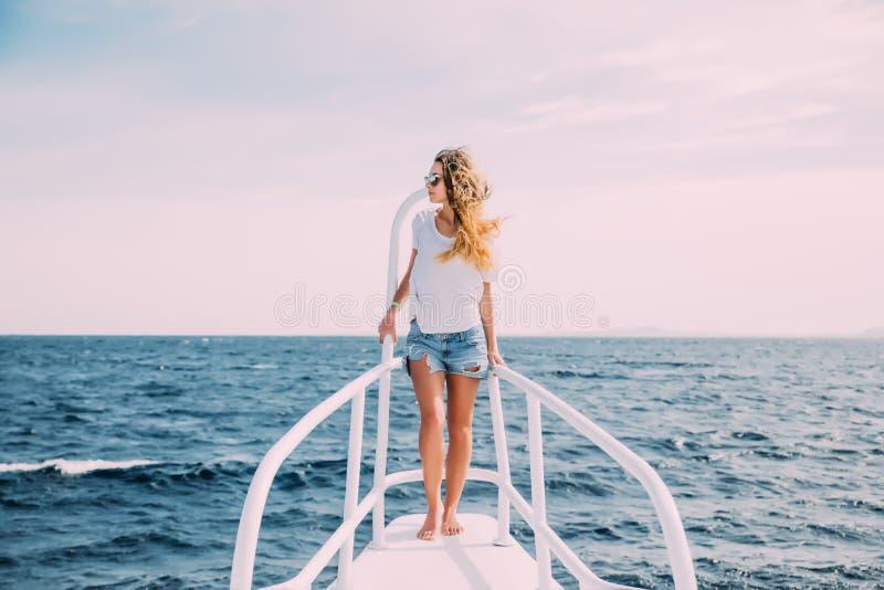 Mujer hermosa que se coloca en la nariz del yate en un día de verano soleado, pelo que se convierte de la brisa, mar hermoso en f imagen de archivo