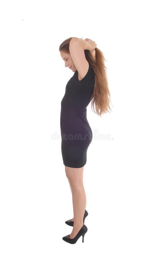 Mujer hermosa que se coloca en un vestido negro imagenes de archivo